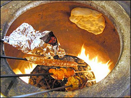 Kebabs and bread cook in a tandoor oven